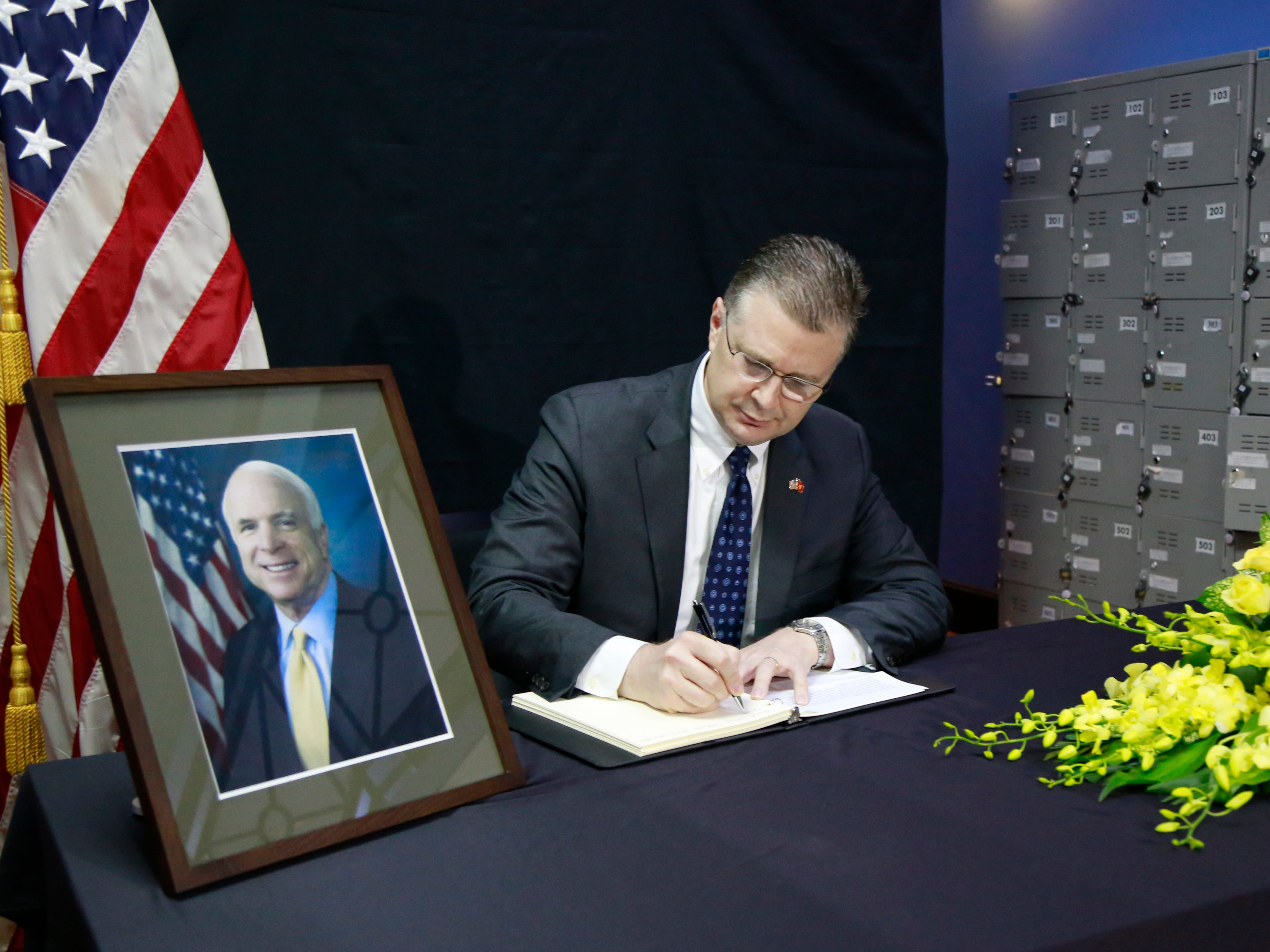 U.S. Ambassador to Vietnam Daniel Kritenbrink writes a note in a book of condolences for the late U.S. Senator John McCain in Hanoi, Vietnam, Aug. 27, 2018.