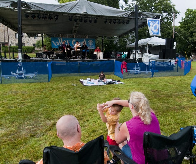 Joshua Maes dances with his mother Majel as his father Chris looks on while Tumbao Bravo plays on the Valley Court Stage during the Great Lakes Folk Festival.