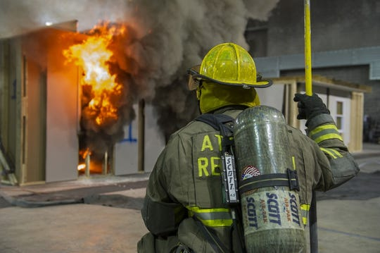 An ATF Firefighter stands by as an enclosure fire burns during the Certified Fire Investigator Candidate (CFIC) course held at the ATF National Fire Research Laboratory on Dec. 11, 2014.