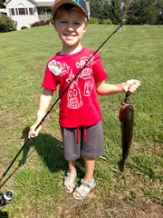 Walter Durning, 4, shows off a bass he caught during a fishing trip with his grandfather, Peter Fanelli of Hyde Park.