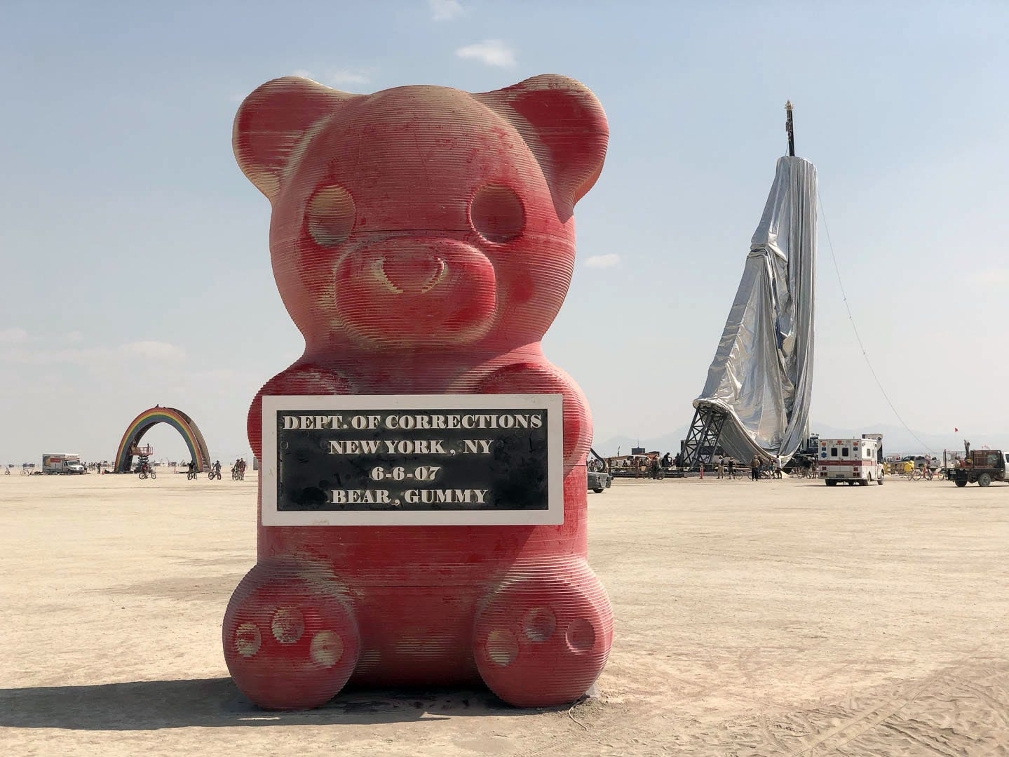 """A giant gummy bear sculpture stands in the playa at Burning Man 2018. To the left, a rainbow stairway and to the right, """"The Orb"""" is under construction."""