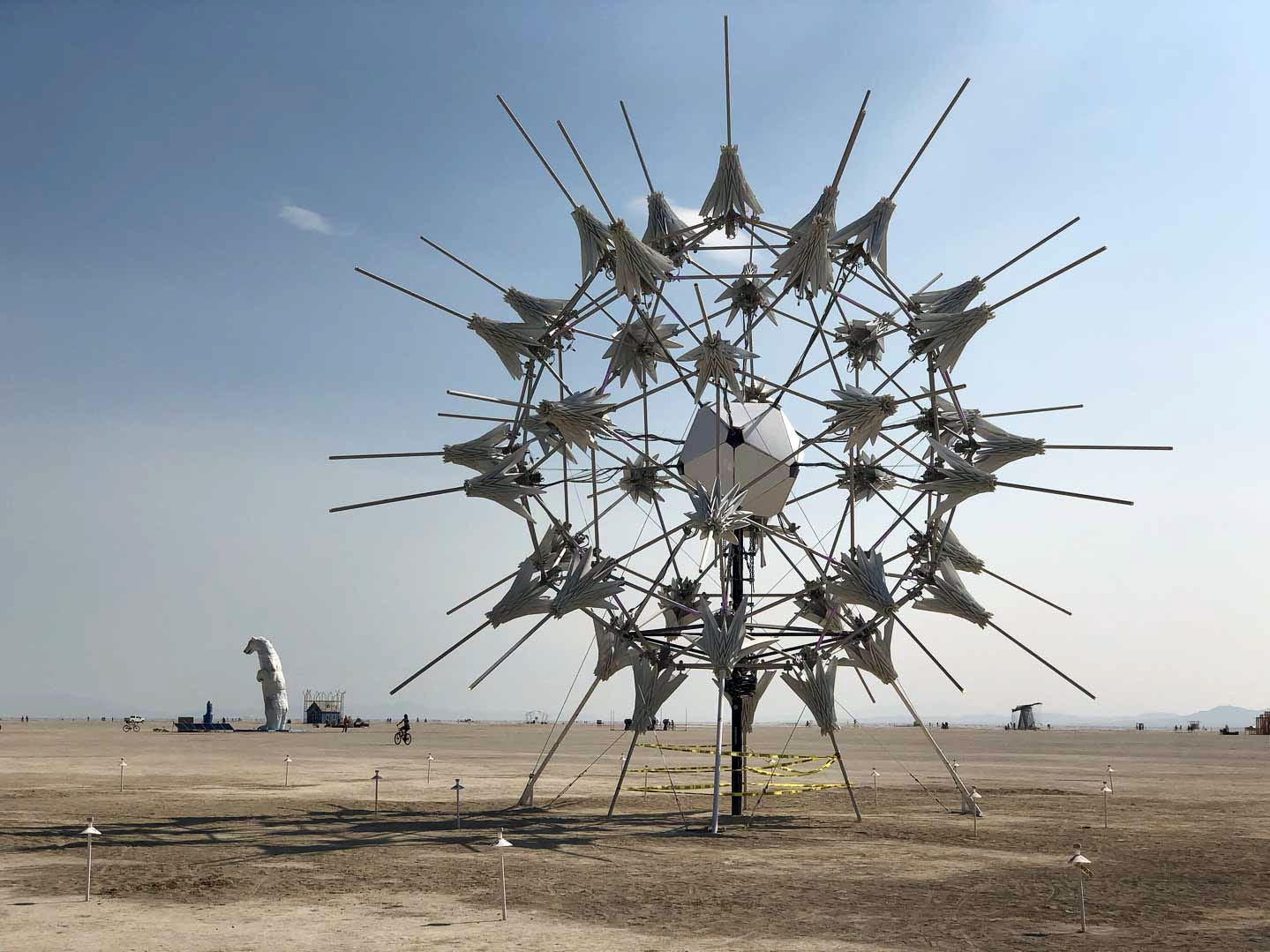 "RadiaLumia, by FoldHaus Collective, sits in the deep playa at Burning Man 2018. RadiaLumia harkens to radialoria, ""a tiny protozoa with intricate mineral skeletons that covered the desert thousands of years ago, when it was once the sea floor,"" according to the artist. To the left, a 34-foot tall polar bear sculpture made of white car hoods stands in the desert to represent the disappearance of polar bears because of greenhouse gases emitted by fossil fuel-burning vehicles."