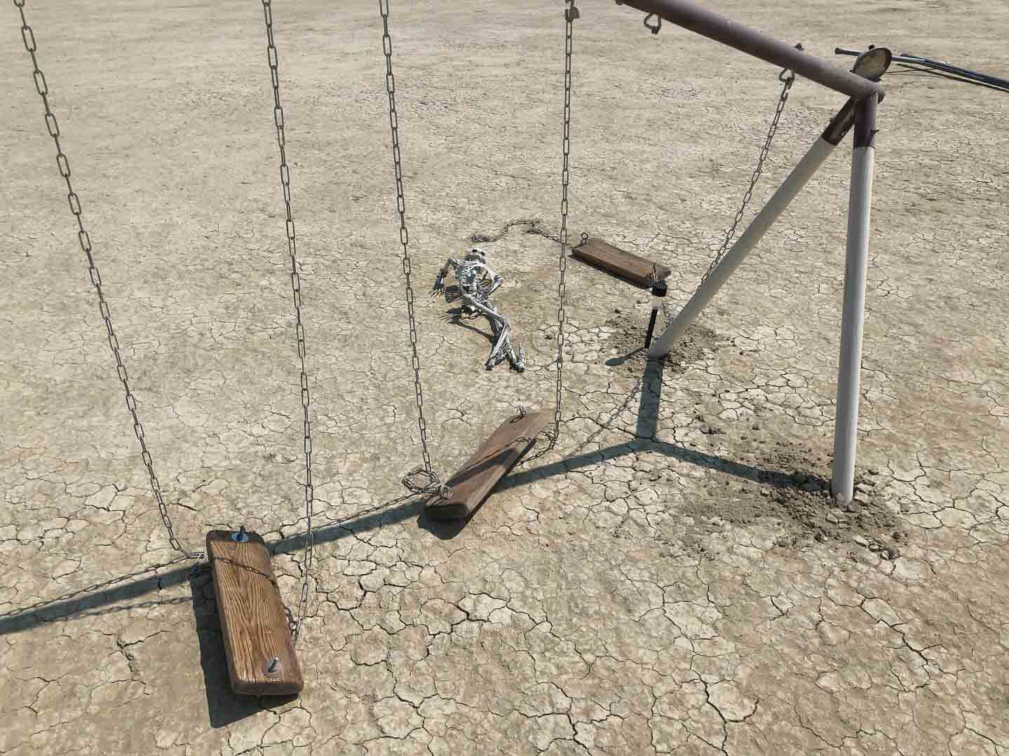 "A destroyed playground rests out in the playa at Burning Man 2018. Skeletons, bicycles, a swing set, an air raid siren create a scene depicting the destruction of humans by robots. The scene is reminiscent of John Connor's nuclear holocaust dream in the ""Terminator"" movies."