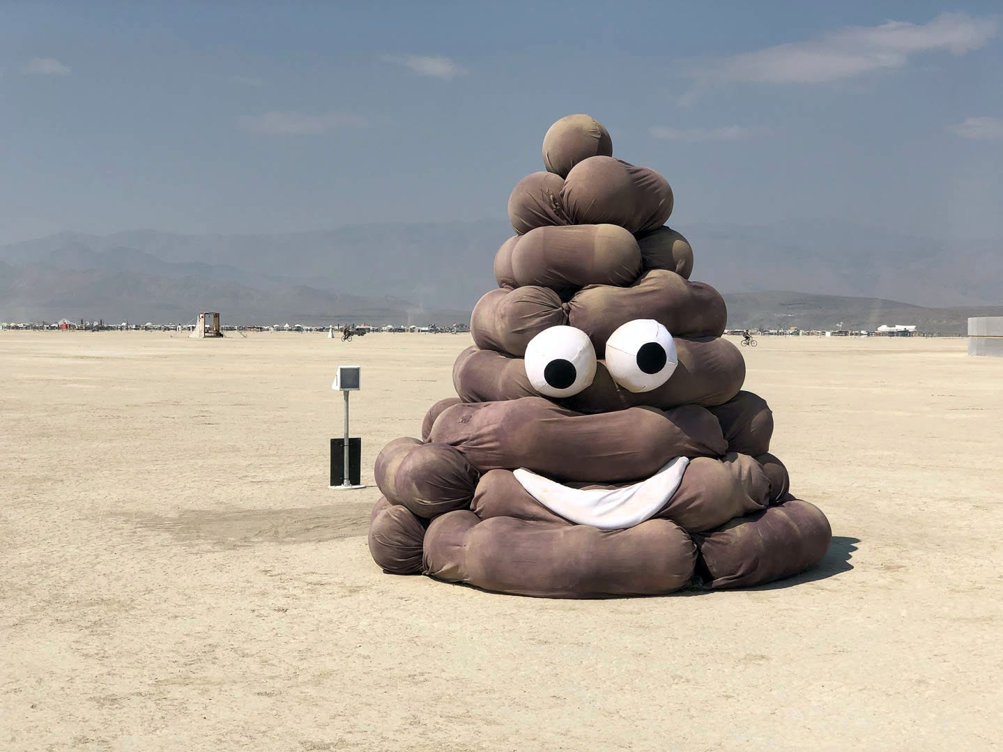 A large poop emoji is in the deep playa near the trash fence at Burning Man 2018.