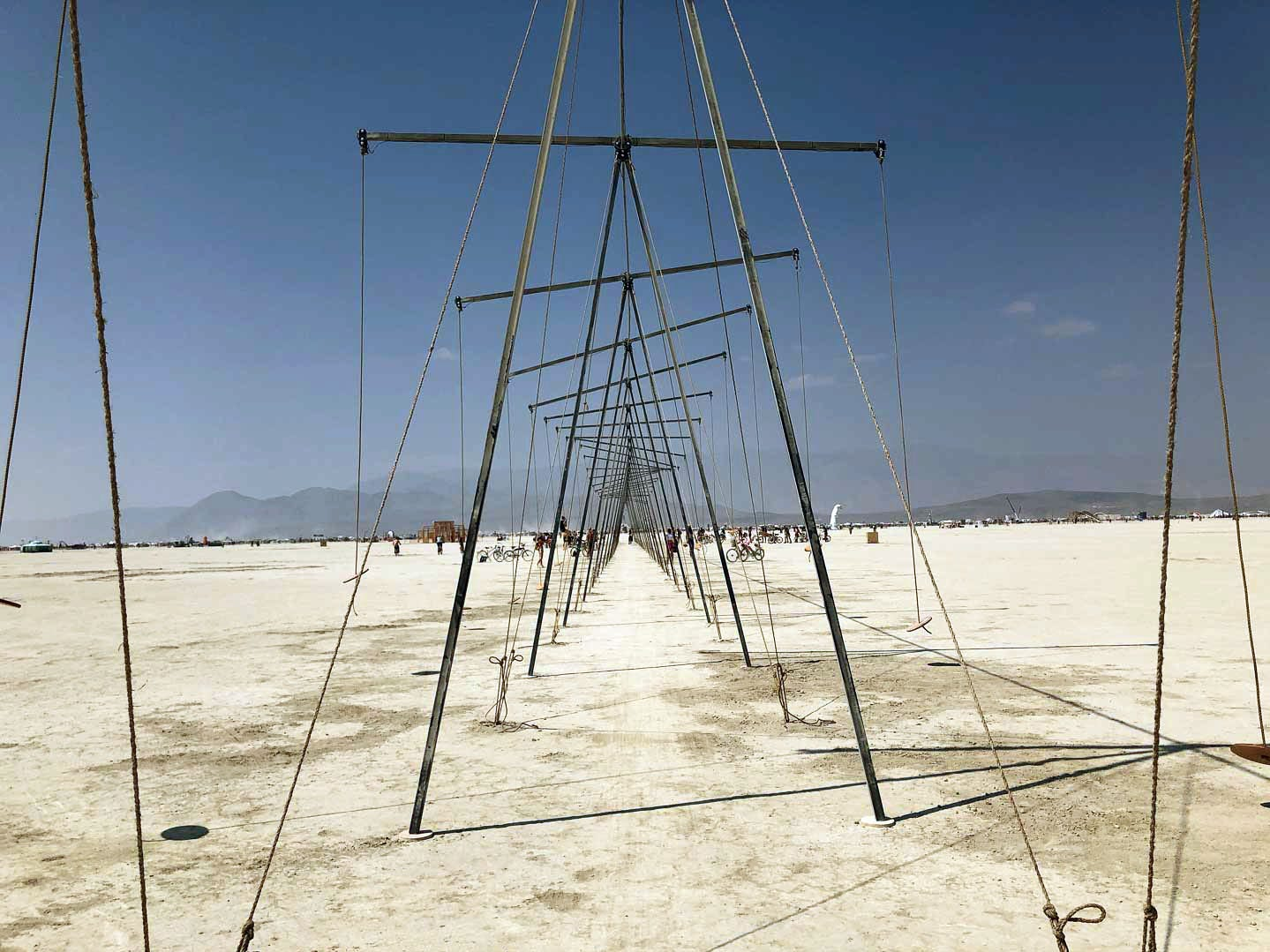 The Seesaw Wave Machine, created by Ryan Elmendorf and Nick Geurts, stands in the playa at Burning Man 2018. The seesaw wave machine is 21 seesaw swings connected across a triangular structure. When people play on the swings, other seesaws start to move.