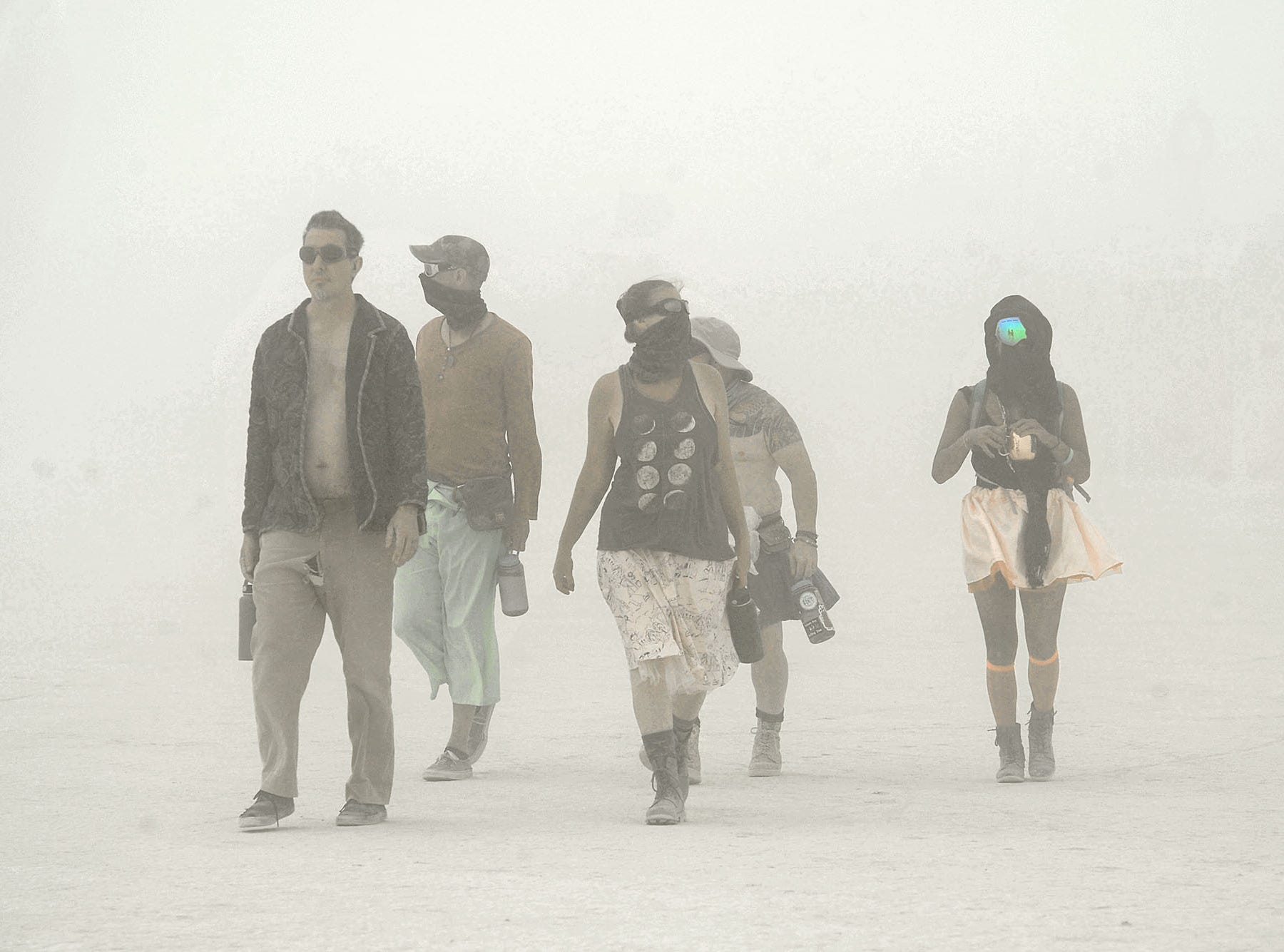 Burners enjoy a walk through a dust storm Sunday, Aug. 26, 2018 at Burning Man in the Nevada desert. The gates into the event were closed due to the storms.