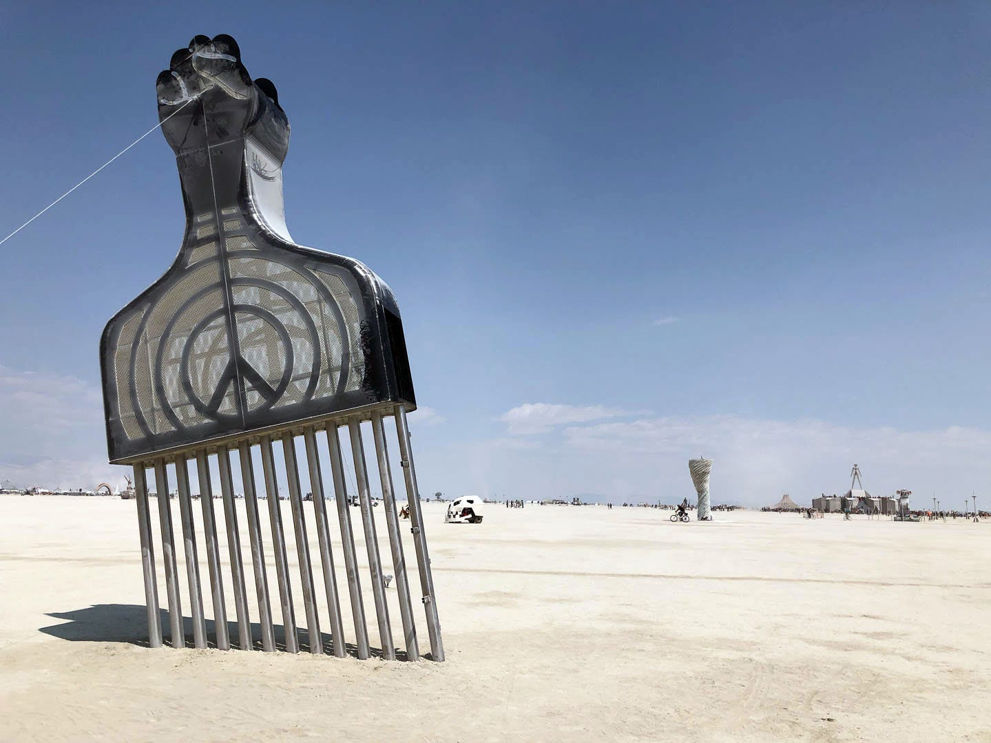 "A large afro pick juts out of the playa at Burning Man 2018. ""A symbol of community and comradeship, the afro pick exists today as many things to different people: it is worn as adornment, a political emblem and signature of collective identity,"" according to the artist's statement. ""The temporary monument would be placed as a symbol and site, to highlight ideas related to community, strength, perseverance, comradeship, and resistance to oppression, equal justice and belonging."