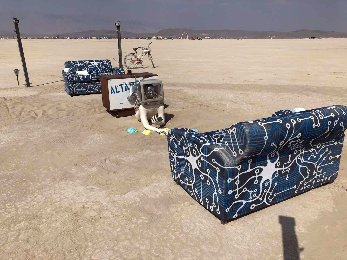 In the deep playa during Burning Man 2018, a scene is arranged with two couches facing a mirrored TV on one side, and a person coming out of a computer, holding a smart phone on the other. Burners are invited to write notes in a notebook on the two couches.
