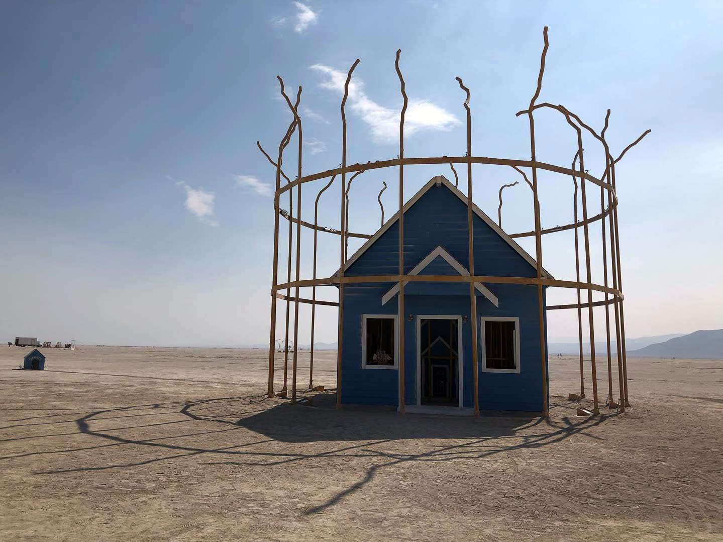 """Singularity"" is a broken bird cage on the playa at Burning Man 2018. It has a house within a house within a house within a house within a house by Rebekah Waites and the Singularity Crew. People can walk inside and interact with the vintage elements, then walk inside the house again and find the same pieces until they can no longer enter the smallest house within."