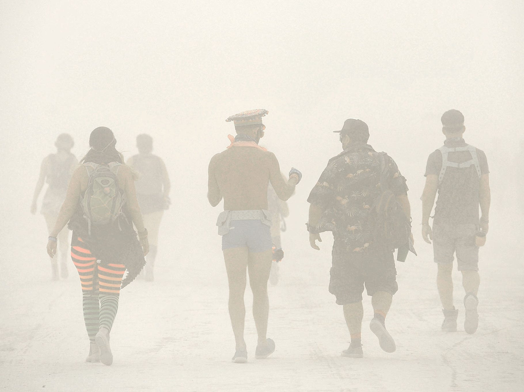 Burners walk and talk during a dust storm on Sunday, Aug. 26, 2018 at Burning Man in the Nevada desert. The storm lasted all day, causing the gates into the event to close while the storm lasted.