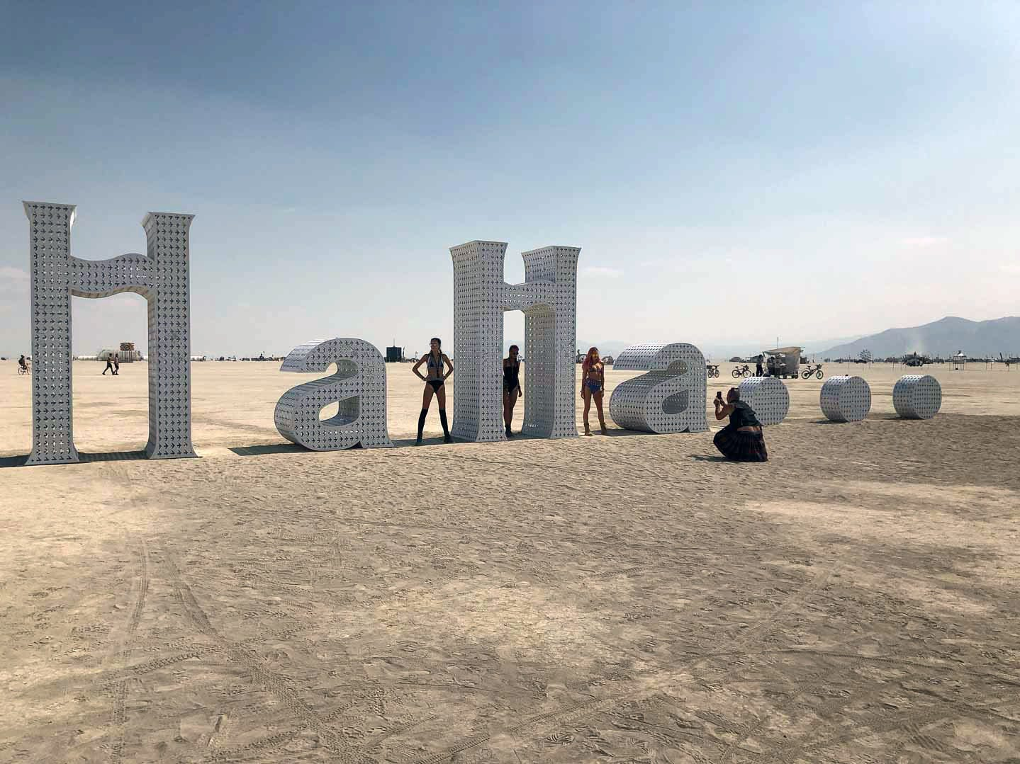 "Jeff Schomberg's sculpture piece at Burning Man 2018, is ""HaHa ..."" Three women pose for a photo on the sculpture. Schomberg's previous pieces include ""Love,"" ""Dream,"" ""Believe."""