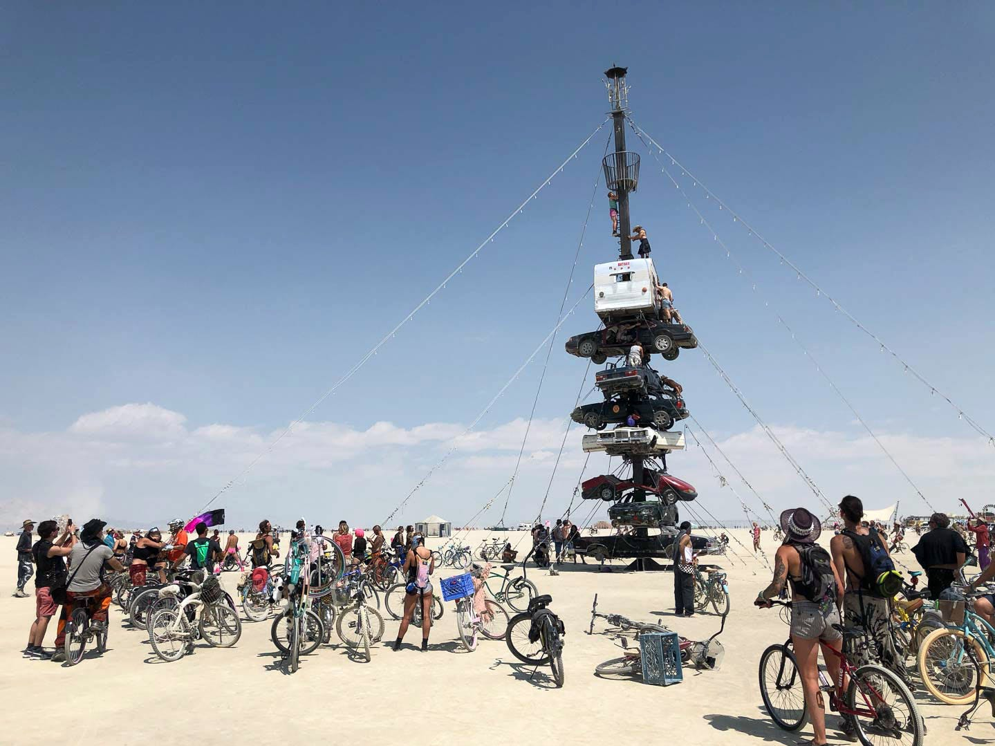 "A multi-story tower of destroyed vehicles juts out of the playa near Black Rock City. Burners are climbing the sculpture while others watch. There is no stairway or safety rails on this sculpture, an example of the Burning Man mantra ""safety third."""