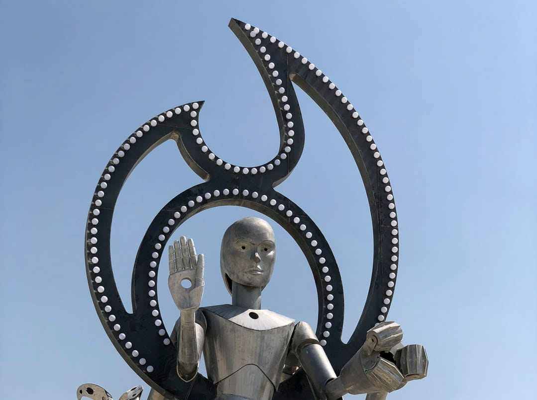 """With Open Arms We Welcomed That Which Would Destroy Us"" by Christian Ristow is a large metal sculpture of a Vishnu-like robot god at Burning Man 2018. The pictographs on the sides show the story of man falling in love with phones, then creating robots who replace relationships with humans, then robots providing and doing all for humans before finally overtaking them, subjugating them and becoming their gods."
