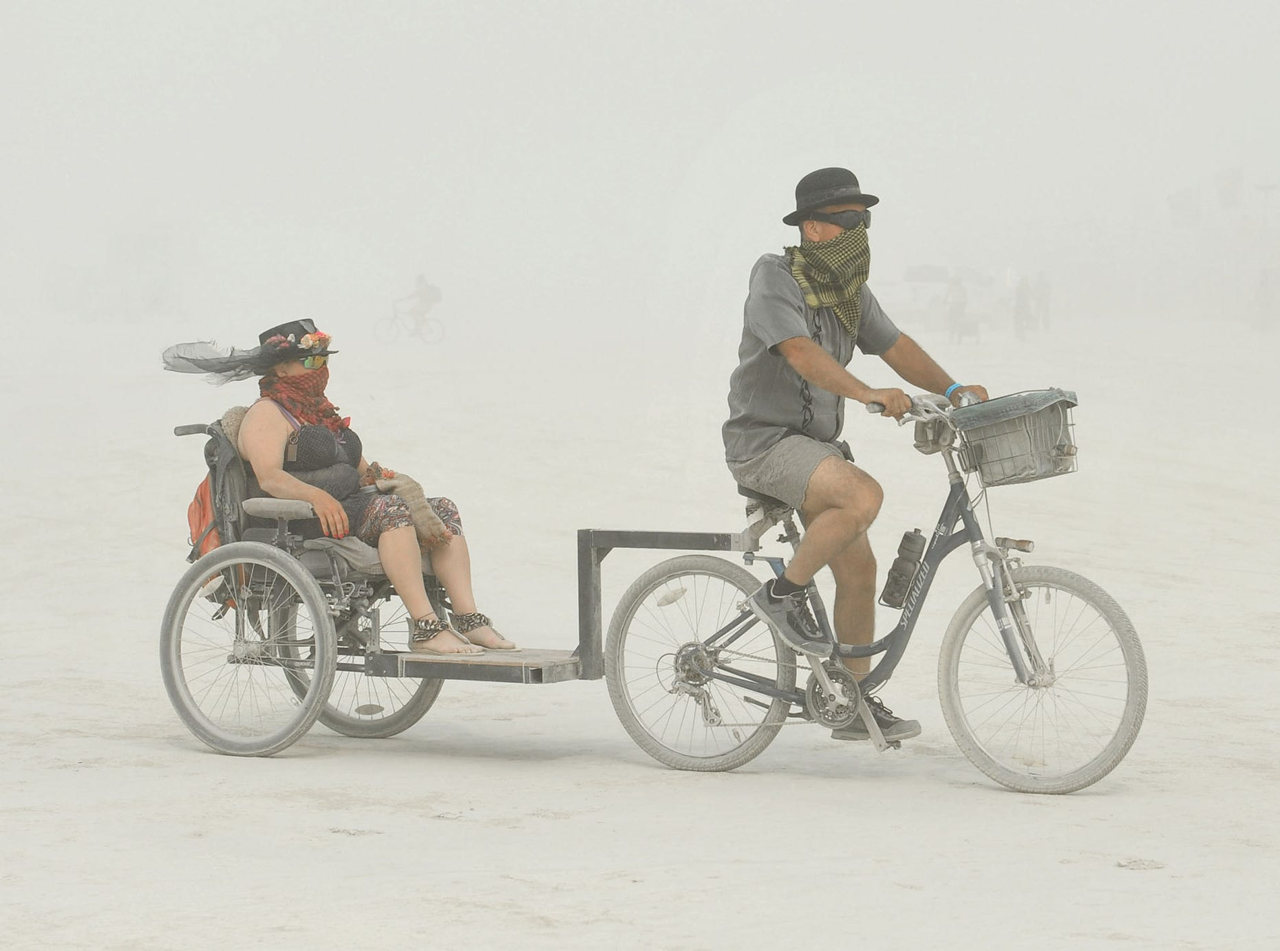 A couple go for a ride in a dust storm Sunday, Aug. 26, 2018 at Burning Man in the Nevada desert. The storm lasted all day, causing the gates into the event to close while the storm lasted.