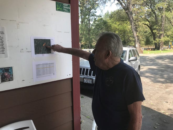 Ross Marshall, 76, owner of the Lakeshore Inn and RV, points to a map of the Hirz Fire damage that's posted outside his resort office on Monday, Aug. 27, 2018.