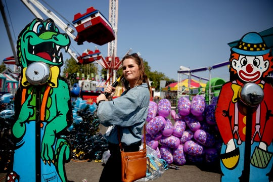 Statesman Journal entertainment reporter Abby Luschei tries the Hi Striker hammer carnival game at the Oregon State Fair in Salem on Tuesday, Aug. 28, 2018.
