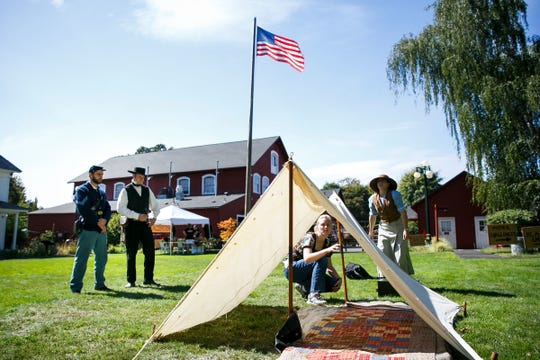 From left, Andrew Engel and Jeff Meek watch as Michelle Bruhn and Serianna Rosberg work together to pitch a tent at the Fort Laramie station at the Oregon Trail Live event on Saturday at the Willamette Heritage Center.