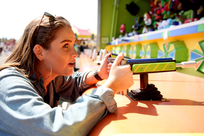 Statesman Journal entertainment reporter Abby Luschei tries a water-shooter carnival game at the Oregon State Fair in Salem on Tuesday, Aug. 28, 2018.