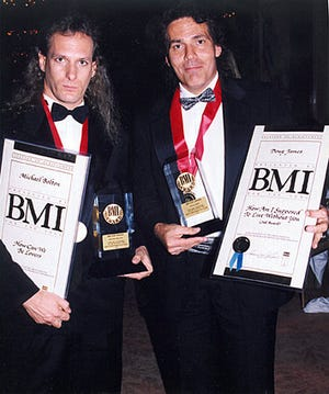 "Michael Bolton and Doug James pose at an awards ceremony. The two wrote ""How Am I Supposed to Live Without You,"" the first of many songs they co-created."