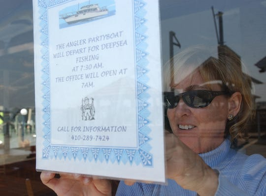 In this 2004 file photo, Jayne (Bunting) Kendall of the Angler hangs up a sign for the Angler Partyboat as she prepares the restaurant for another season in Ocean City.