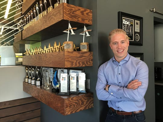 Eric Sivertsen, CEO and partner of Epicosity, stands next to his company's numerous awards, including multiple Inc. 5000 listings.