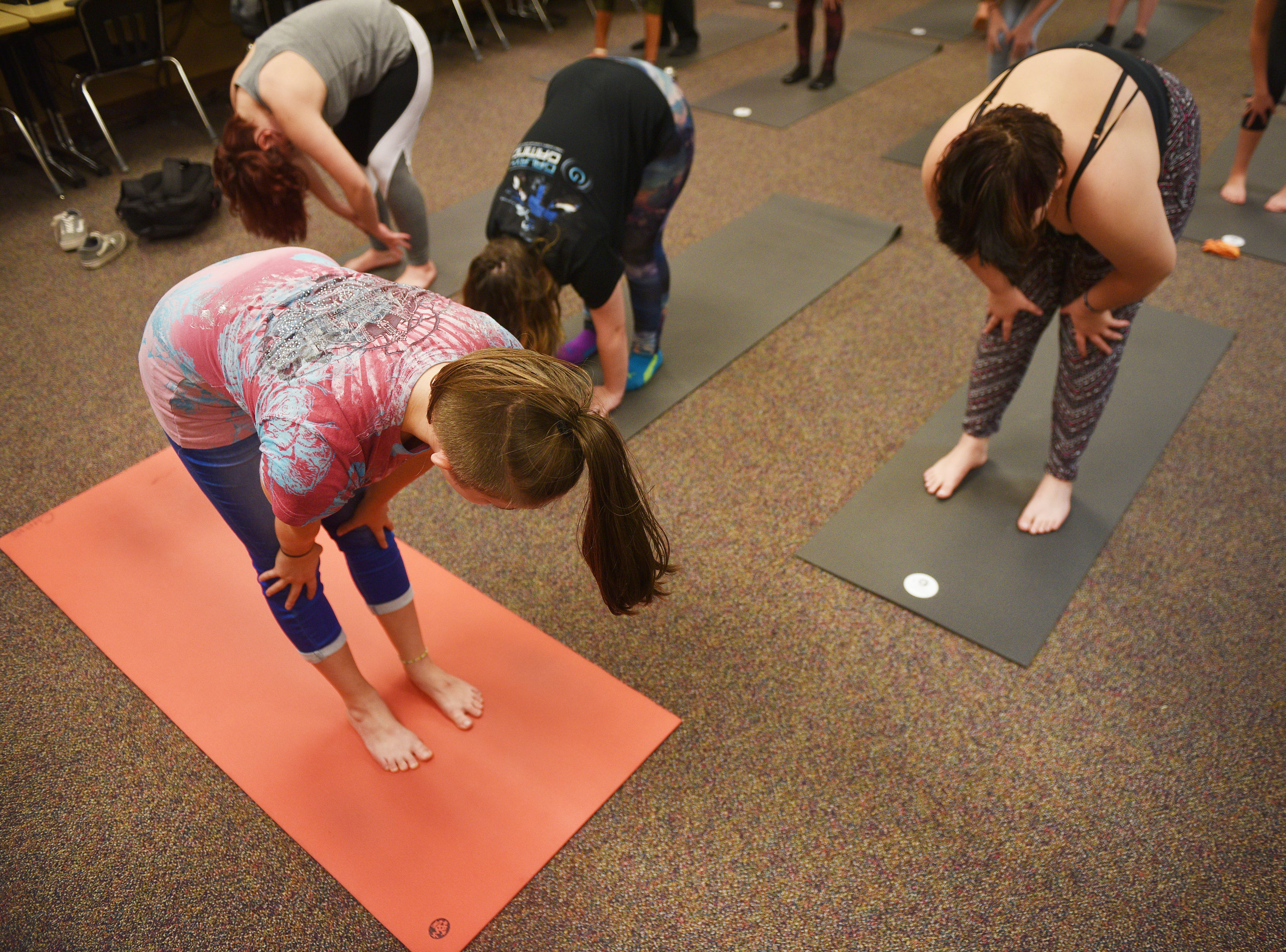 New Tech High School teacher Chris Coughlin has New Tech High School senior Emma Sivering, left, help lead the yoga class Tuesday, Aug 28, in Sioux Falls. Sivering is working towards becoming a certified yoga instructor.