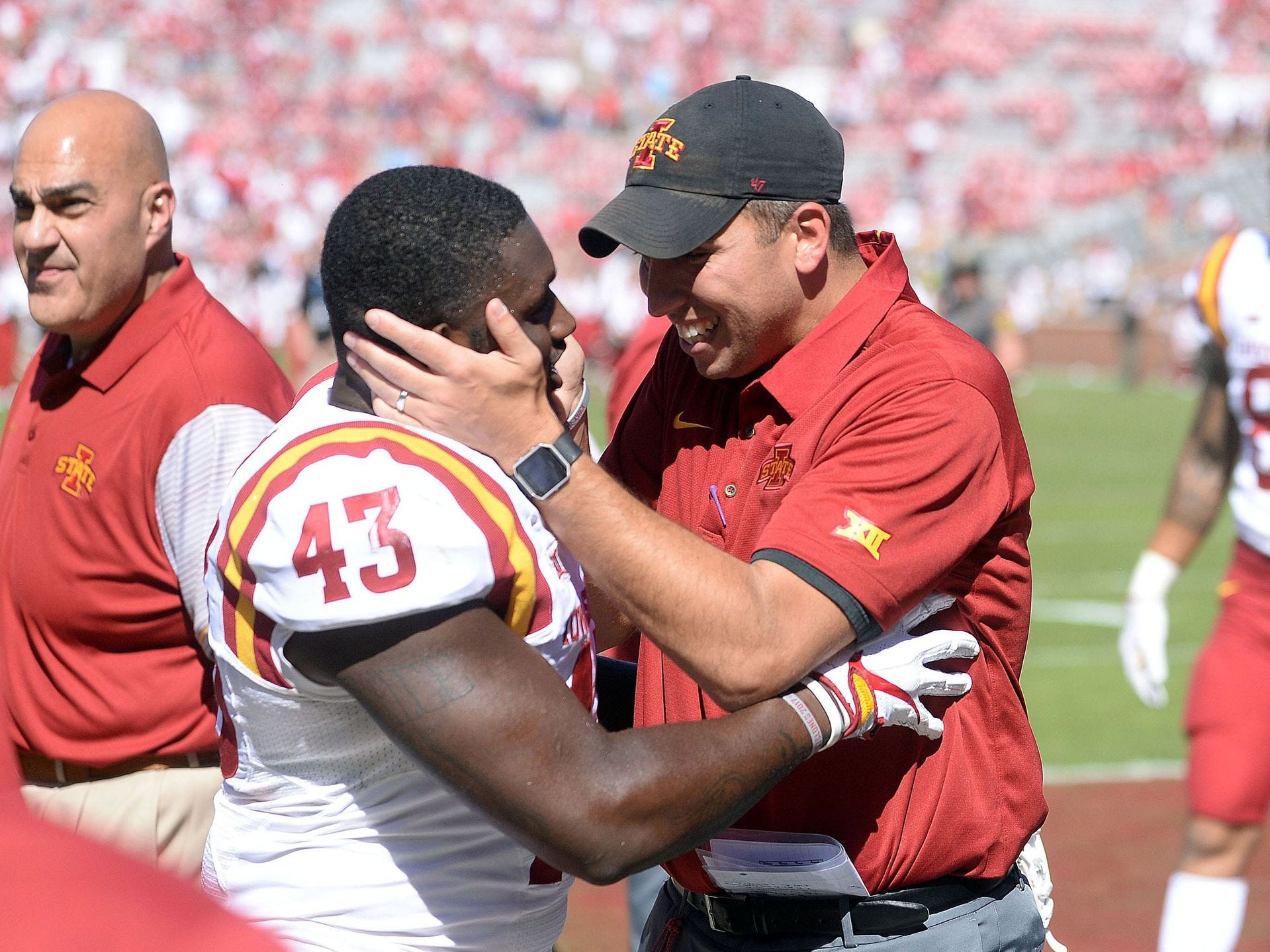 Coach Matt Campbell (right) celebrates a win over Oklahoma with one of his players last season