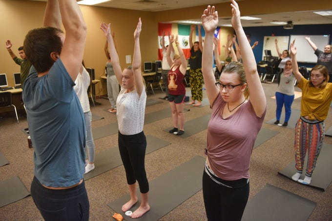 New Tech High School student Rebecca Hanson, right, and Presli Peterson, center, follow along with teacher Chris Coughlin, left, during yoga class Tuesday, Aug 28, in Sioux Falls. The class has been added as an extra curricular.
