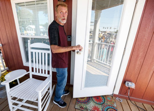 Tommy Yarberry looks back at the crowd after opening the door to his new home during the Eden Village Grand Opening Ceremony on Tuesday, Aug. 28, 2018. Yarberry is the first resident in the tiny home community.