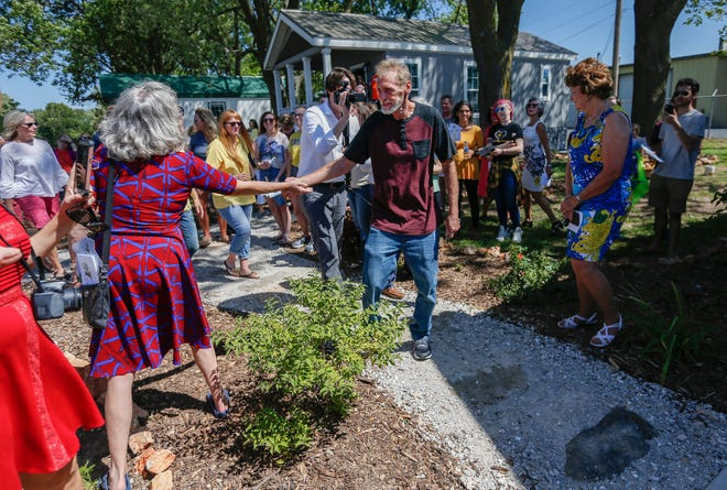 Tommy Yarberry shakes hands with people as he walks to his new home during the Eden Village Grand Opening Ceremony on Tuesday, Aug. 28, 2018.
