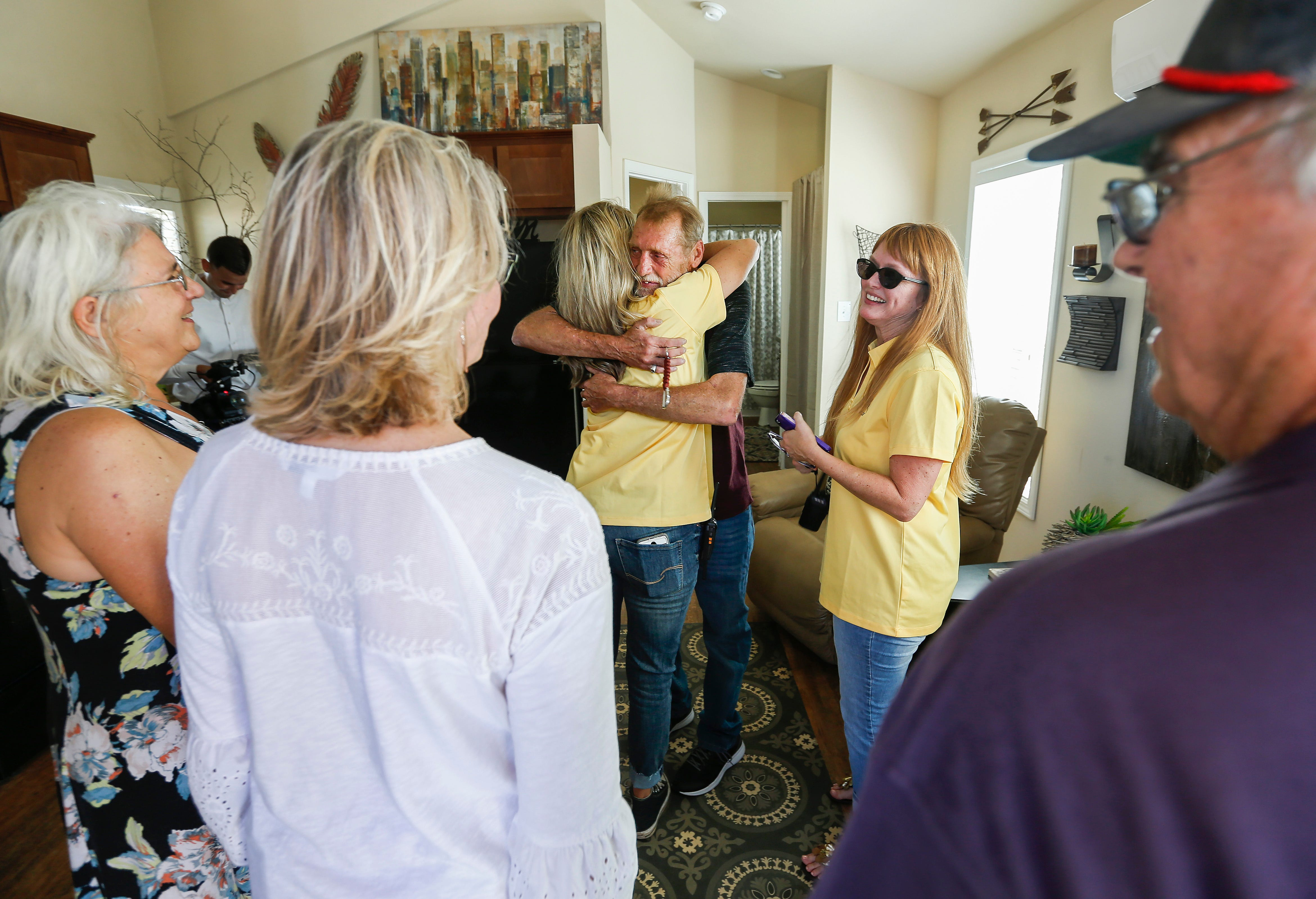 Tommy Yarberry hugs Cherie Roderick after walking into his new home during the Eden Village Grand Opening Ceremony on Tuesday, Aug. 28, 2018. Yarberry is the first resident to move into the tiny home community.
