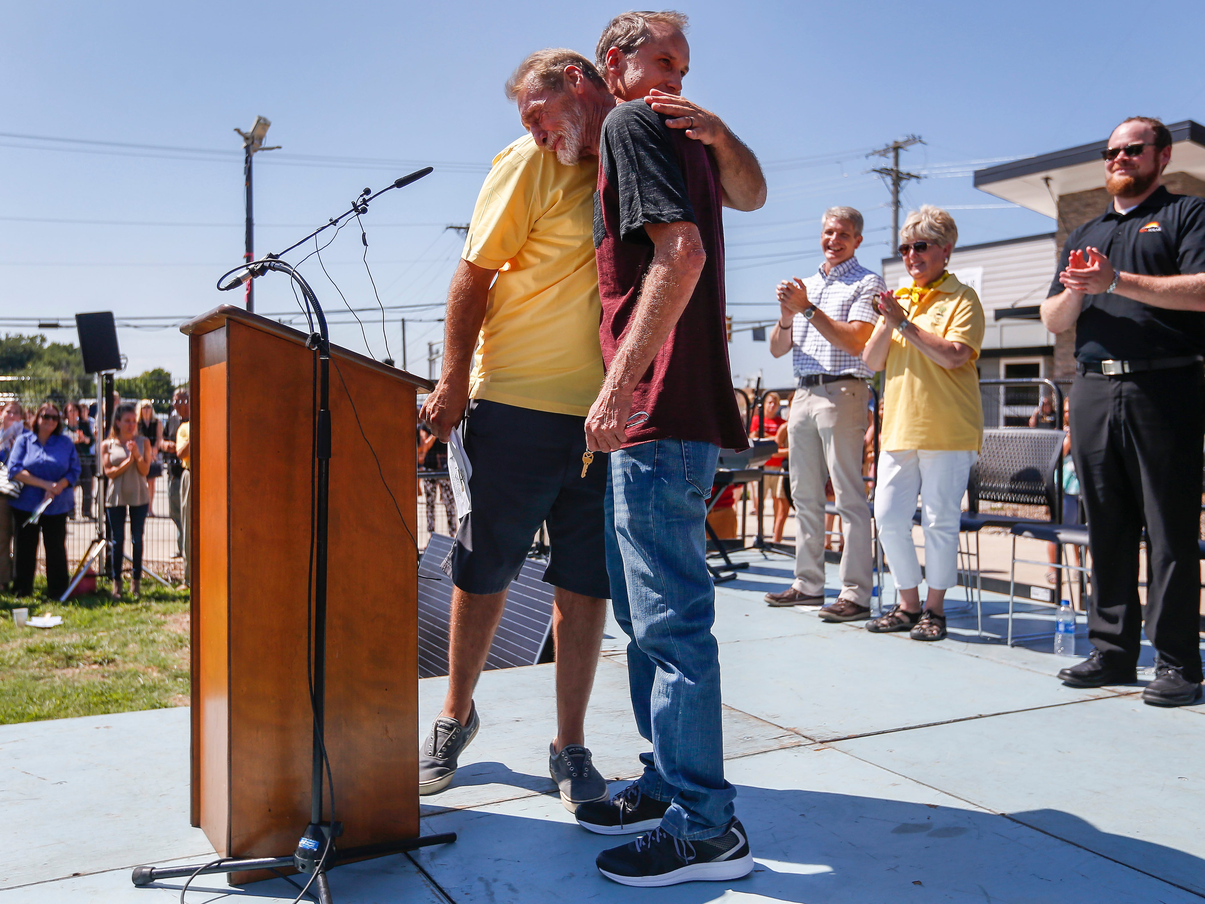 Nate Schlueter, COO of Eden Village, hugs Tommy Yarberry after handing him the keys to the first tiny home during the Eden Village Grand Opening Ceremony on Tuesday, Aug. 28, 2018.
