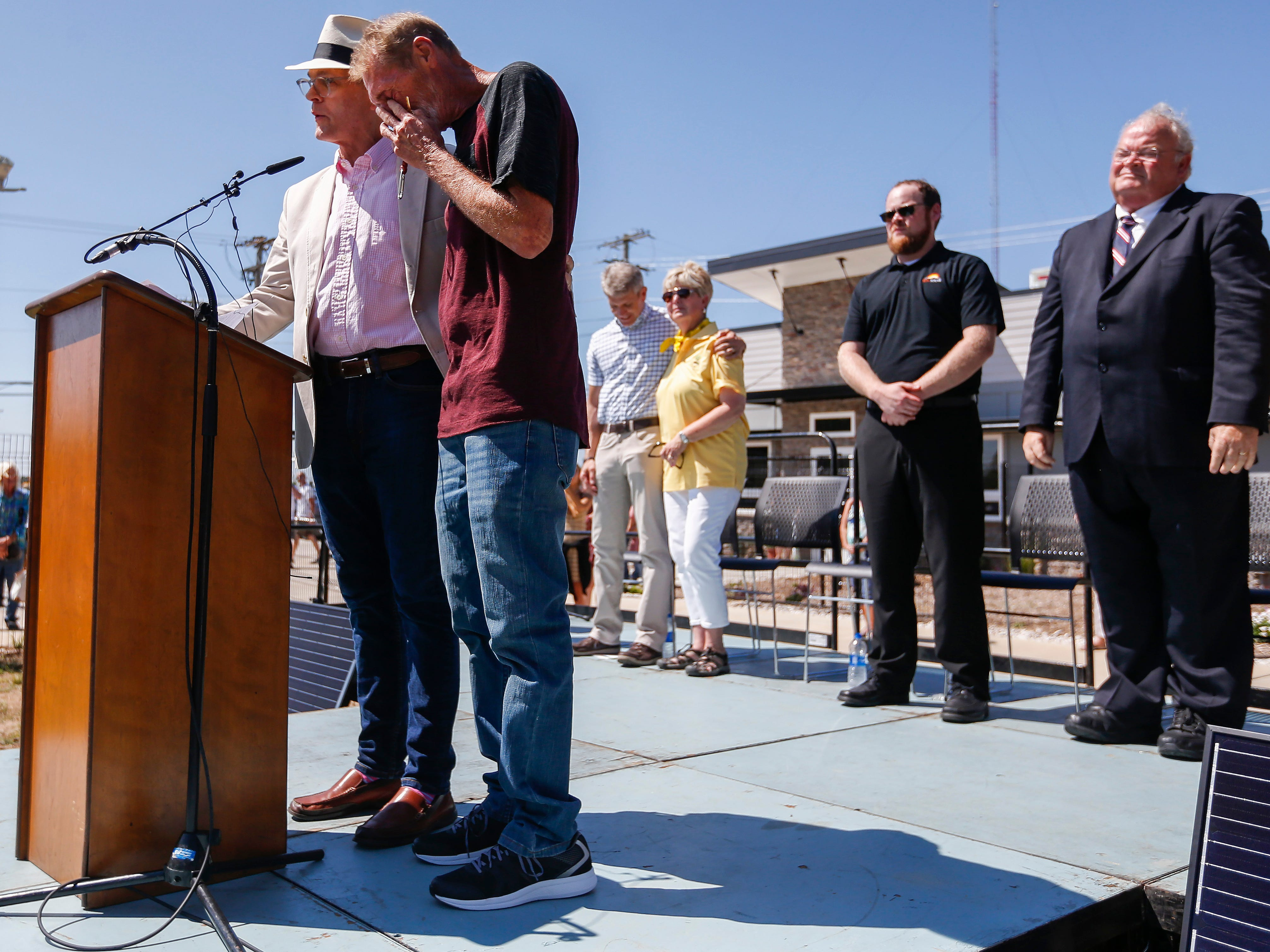 Tommy Yarberry, right, wipes a tear from his eye as Pastor Phillip Wright says a prayer for him during the Eden Village Grand Opening Ceremony on Tuesday, Aug. 28, 2018.