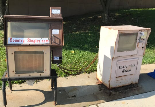 The Los Angeles Times newsbox is chained to a CountrySingles.com box.