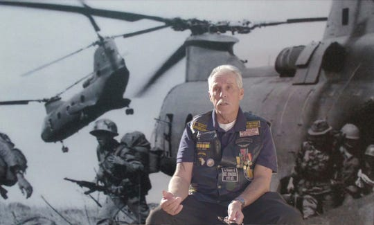 "Dan Greathouse, President, Vietnam Veterans of America, Chapter 961 talks about his experiences in front of a photo of Chinooks in the documentary ""Dreams of the Black Echo."""