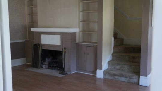 The fireplace in living room and stairway leading to the second floor.