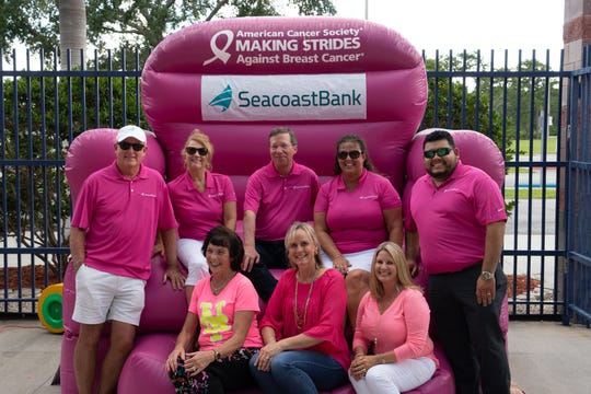 """Poised on the Giant Pink Chair at Paint the Park Pink at First Data Field on Aug. 4 are, from left, back row: Seacoast Bank Volunteers and Sponsor Leader Tom Hall, also a Real Men Wear Pink candidate for Martin County; Vanessa Farnes, St. Lucie Volunteer Team Leader; Dennis """"Denny"""" S. Hudson III, Seacoast Bank chairman and CEO; Kneli Spencer, Indian River Volunteer Team Leader; Jose Acosta, Real Men Wear Pink for St Lucie County. Front row:  Making Strides Against Breast Cancer Treasure Coast Event Leaders Denise Averill, St. Lucie County; Laura McGarry, Indian River County; and Heather McAdams, Martin County."""