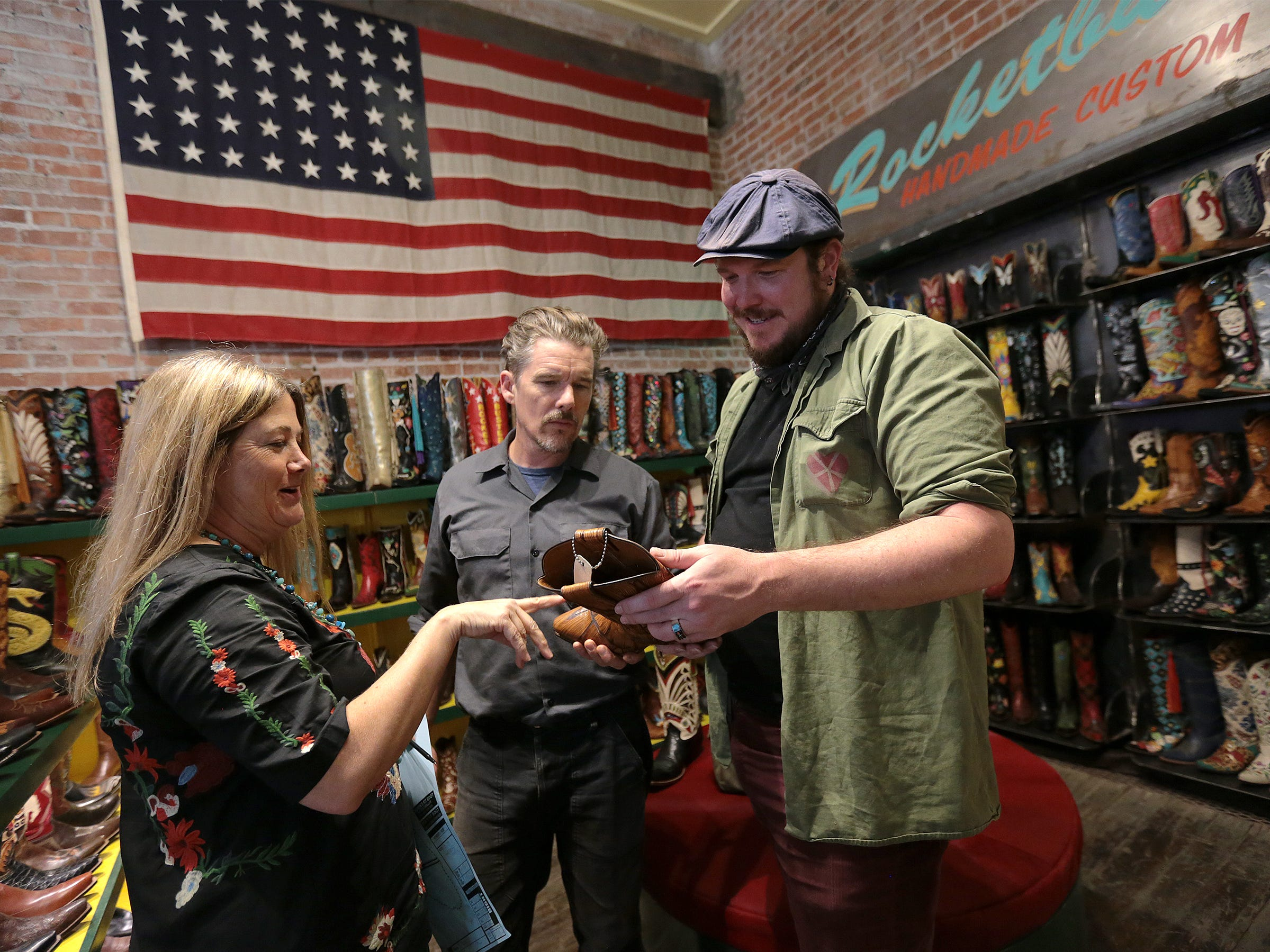 Rocketbuster Boots owner Nevena Christi shows a pair of custom boots to Ethan Hawke and Ben Dickey as they tour the shop in downtown El Paso Tuesday.