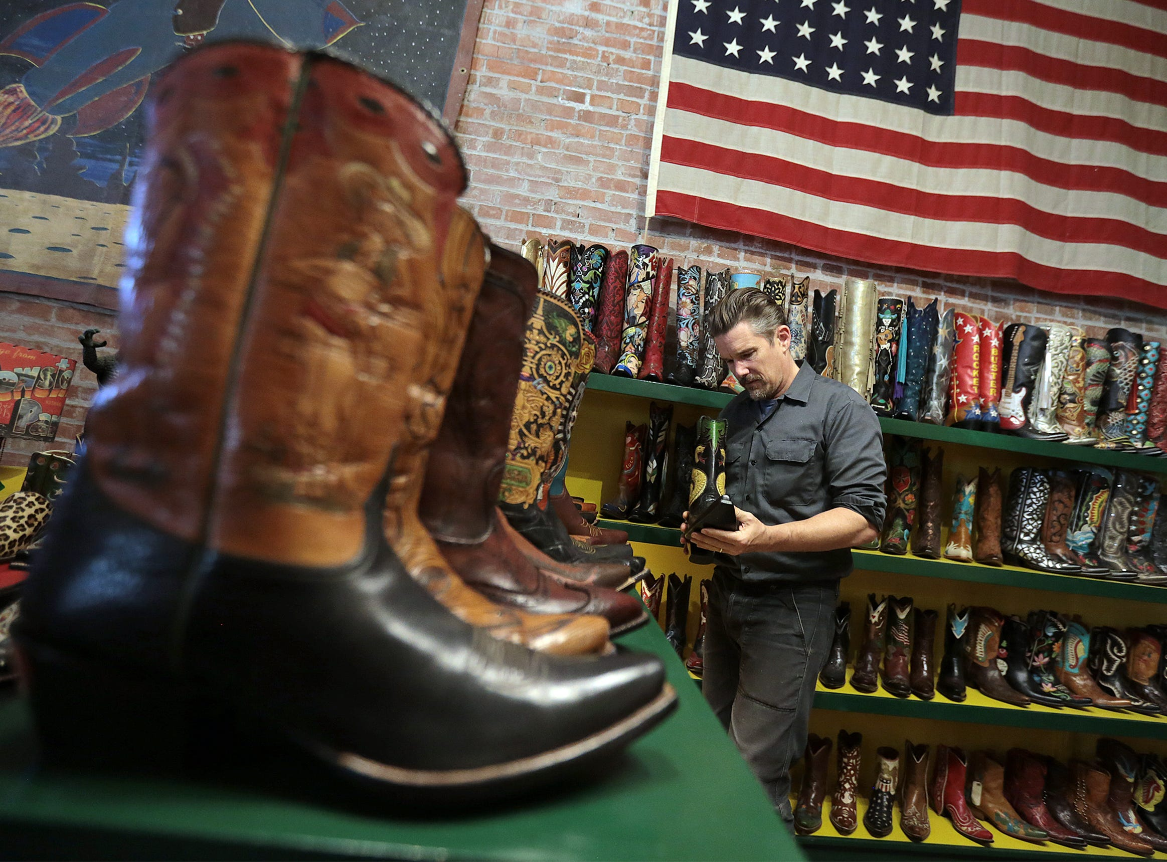 "Actor/director Ethan Hawke peruses the boots at Rocketbuster Boots in Downtown El Paso on Tuesday. Hawke, who directed and co-wrote the film ""Blaze"" about Texas musician Blaze Foley, was in town promoting the film."