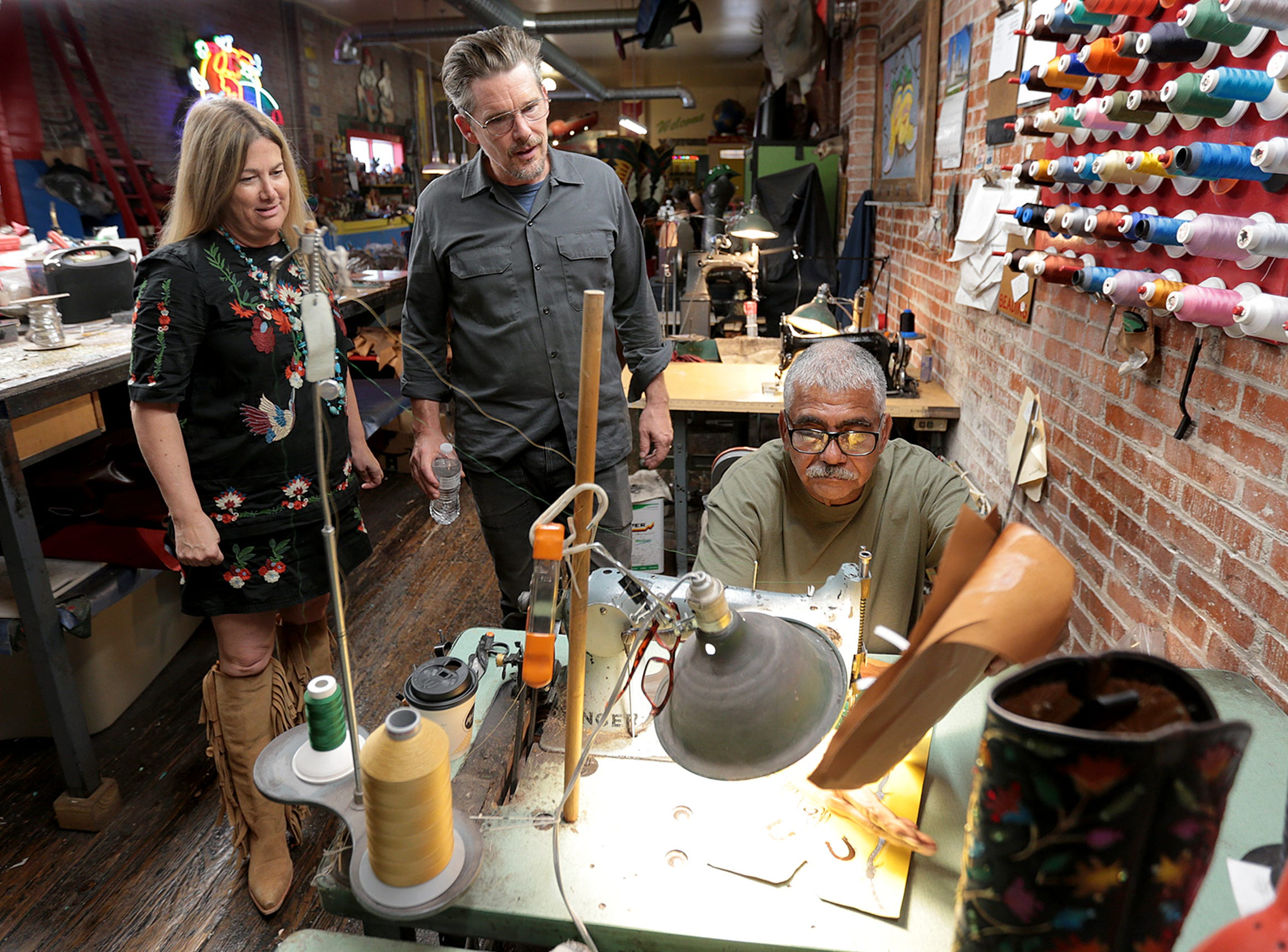Ethan Hawke and Rocketbuster Boots owner Nevena Christi watch as Raul Chavez stiches a pair of boots Tuesday in their downtown El Paso shop.