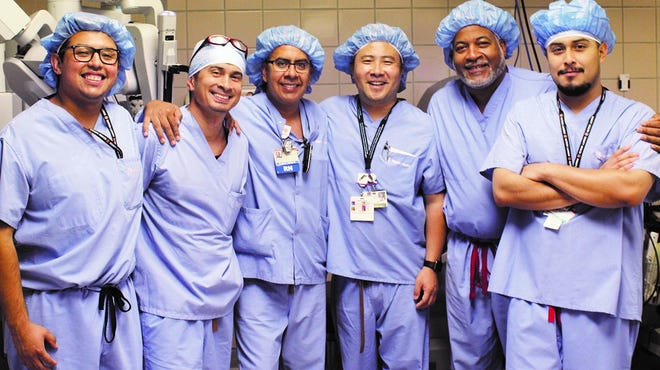 Third from right is Brian Tuai, medical director of robotic surgery at St. John's, and second from right is James McPherson, cardiothoracic surgeon.