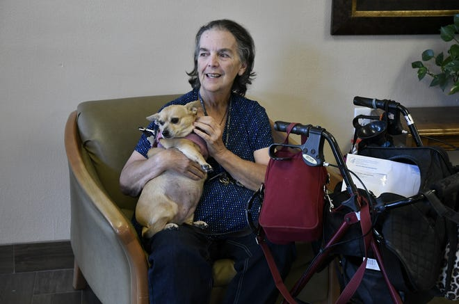 Town Meadows resident Darlene Fowler holds dog Cindy Lou in the senior living facility's lobby on Monday, Aug. 27, 2018.