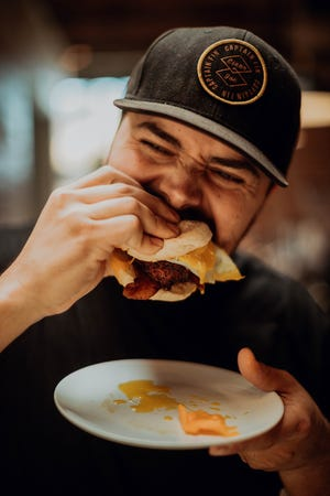 Component Coffee Lab co-owner Jonathon Anderson enjoys a breakfast sandwich. The cafe is opening a new Tulare location with Quesadilla Gorilla next spring.