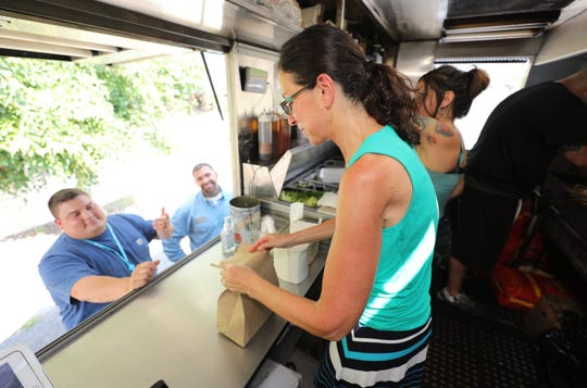 Jeanne Muchnick, the lohud.com food writer, wraps a lunch for Joe Parinello and Anthony Pratarelli as she works the counter of The Souvlaki Truck on Central Park Avenue in Yonkers, Aug. 28, 2018.