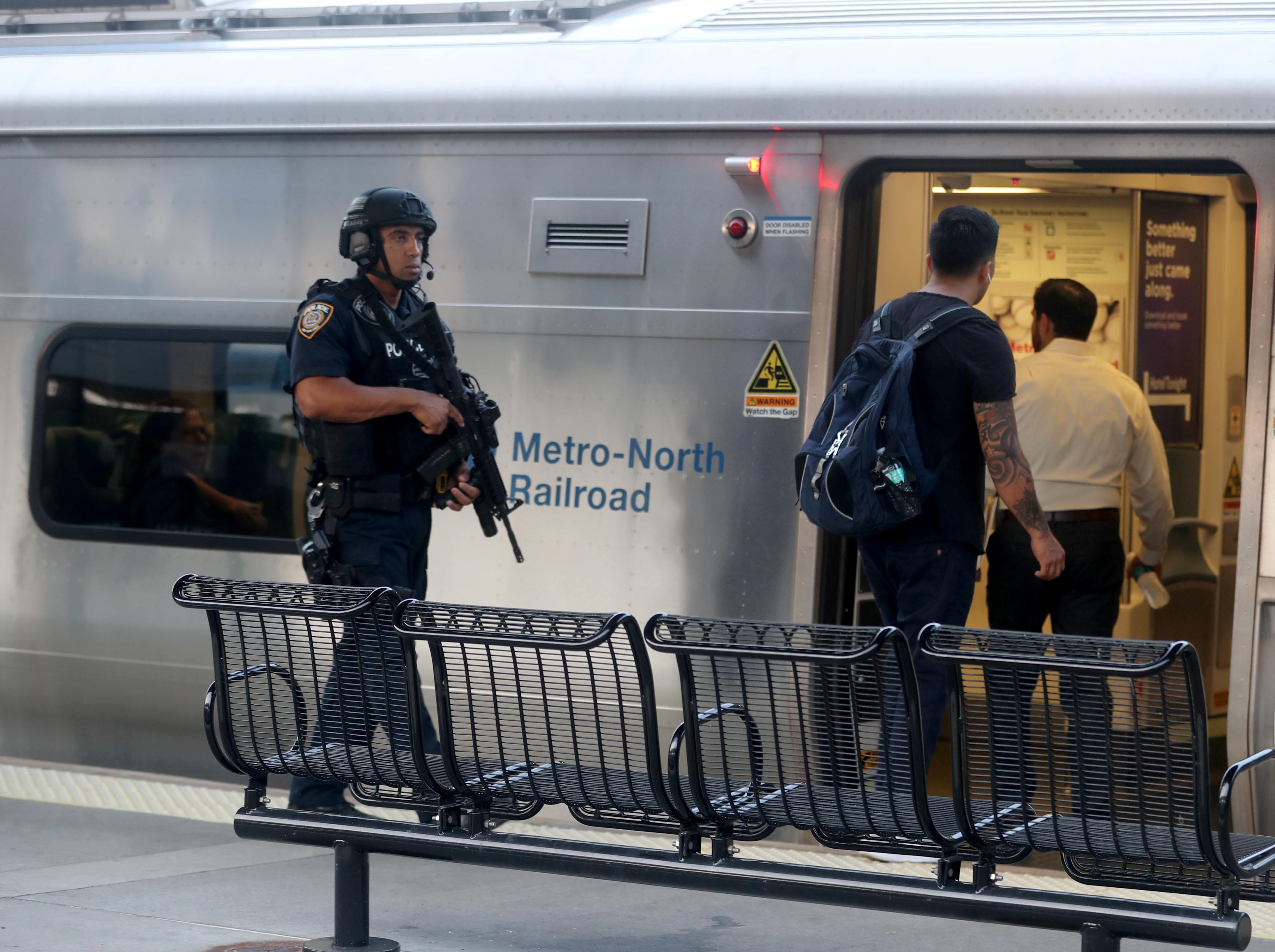 An MTA police officer stands on the platform as passengers board a New York City bound Metro-North train at the Croton-Harmon station during a multi-department safety drill Aug. 28, 2018. Officers from the MTA, Amtrak, Croton Harmon, New York State Police, TSA, and Department of Homeland Security departments took part in the drill during the morning rush hour. The drill involved heightened platform patrols, increased security presence onboard trains, explosives detection canine sweeps, and counter-surveillance measures. Similar drills were also held at several other Hudson Line stations during the morning commute.