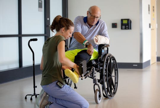 William Lytton, of Scarsdale, right, is assisted by physical therapist Caitlin Geary, left, at Spaulding Rehabilitation Hospital, in Boston, Tuesday, Aug. 28, 2018, while recovering from a shark attack. Lytton suffered deep puncture wounds to his leg and torso after being attacked by a shark on Aug. 15 while swimming off a beach, in Truro, Mass. Lytton injured a tendon in his arm while fighting off the shark.