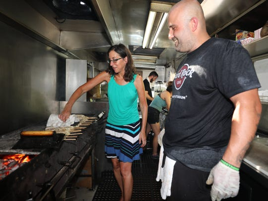 George Kringas, the owner and chef of The Souvlaki Truck, watches as Jeanne Muchnick works the grill at his spot on Central Park Avenue in Yonkers, Aug. 28, 2018.