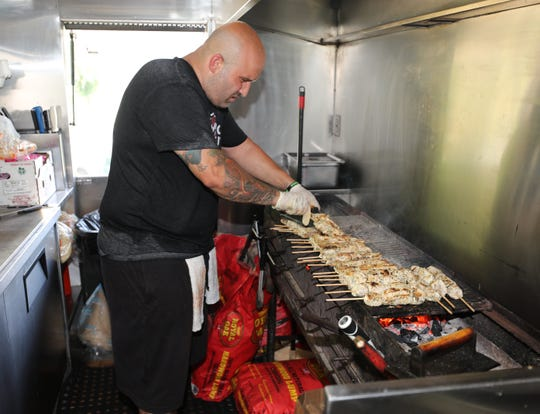 George Kringas, the owner and chef of The Souvlaki Truck, mans the grill at his spot on Central Park Avenue in Yonkers, Aug. 28, 2018.