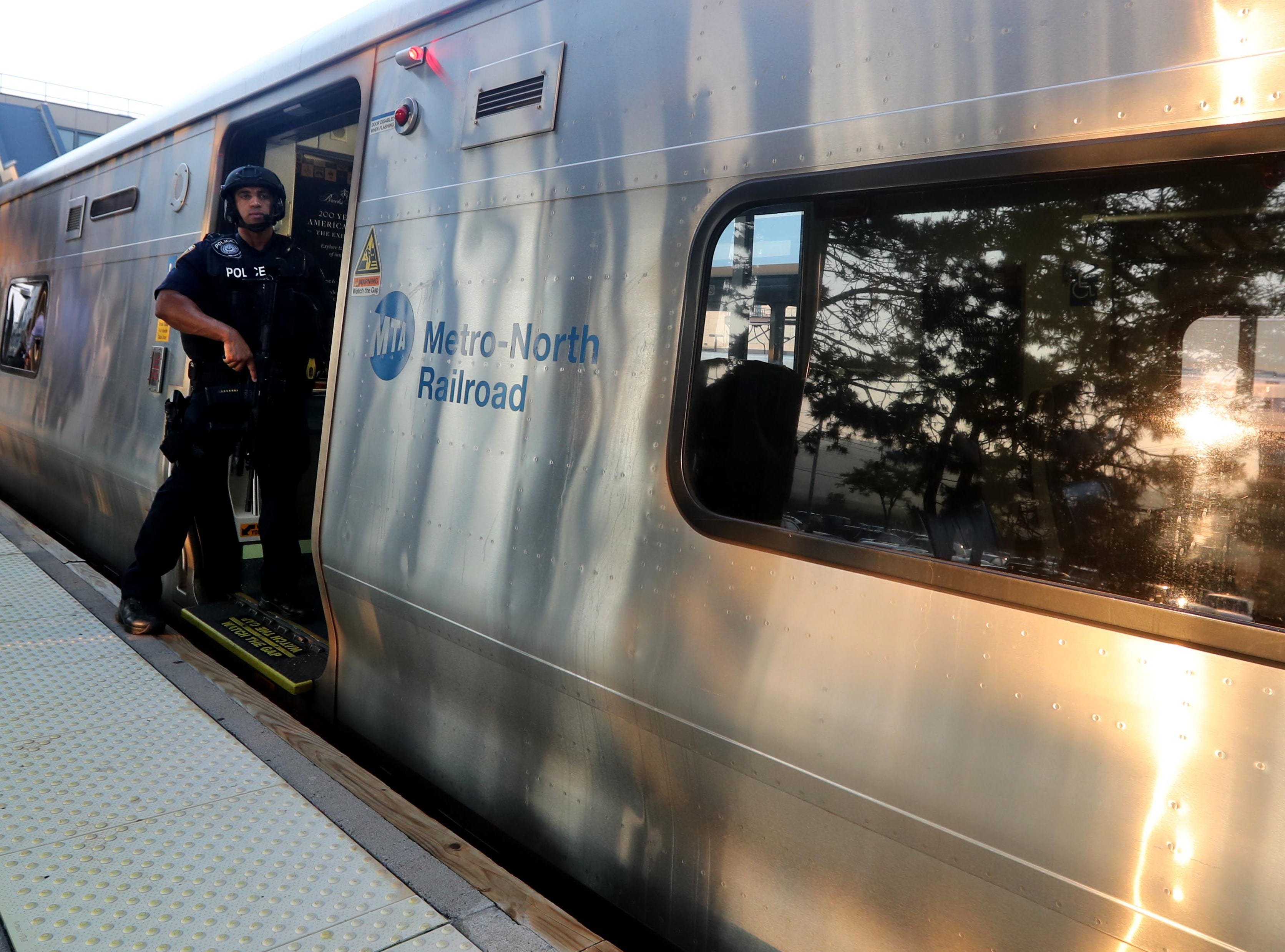 An MTA police officer stands in the entrance of a New York City bound train at the Croton-Harmon station during a multi-department safety drill Aug. 28, 2018. Officers from the MTA, Amtrak, Croton Harmon, New York State Police, TSA, and Department of Homeland Security departments took part in the drill during the morning rush hour. The drill involved heightened platform patrols, increased security presence onboard trains, explosives detection canine sweeps, and counter-surveillance measures. Similar drills were also held at several other Hudson Line stations during the morning commute.