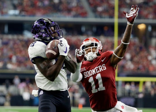 File-This Dec. 2, 2017, file photo shows TCU wide receiver Jalen Reagor (18) catching a touchdown pass in front to Oklahoma cornerback Parnell Motley (11) in the first half of the Big 12 Conference championship NCAA college football game in Arlington, Texas.  Whoever is at quarterback for TCU will be surrounded by talented skill players. Speedy receivers Reagor and KaVontae Turpin have both shown their big-play ability, while Darius Anderson and Sewo Olonilua may be the best running back duo in the Big 12.  (AP Photo/Tony Gutierrez, File)